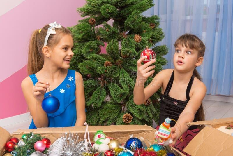 Δύο κορίτσια τραβούν τα παιχνίδια Χριστουγέννων από τα κιβώτια μπροστά από ένα τεχνητό χριστουγεννιάτικο δέντρο στοκ φωτογραφία