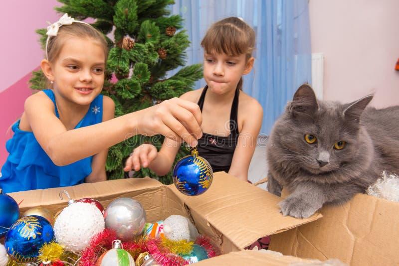 Δύο κορίτσια τραβούν τα παιχνίδια Χριστουγέννων από το κιβώτιο και παρουσιάζουν τη γάτα στοκ εικόνες