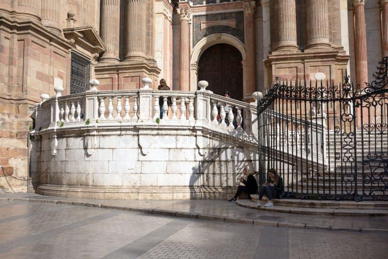 Μάλαγα, Ισπανία, το Φεβρουάριο του 2019 Δύο κορίτσια χαλαρώνουν στα μαρμάρινα βήματα του διάσημου ενσαρκωμένου καθεδρικού ναού Ma στοκ εικόνα