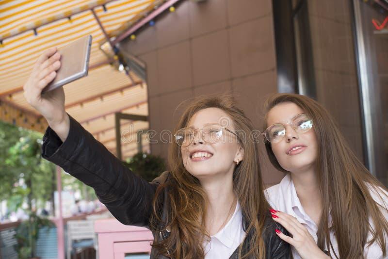 Δύο κορίτσια eyeglasses που κάνουν ένα selfie στο θερινό καφέ στοκ εικόνες με δικαίωμα ελεύθερης χρήσης
