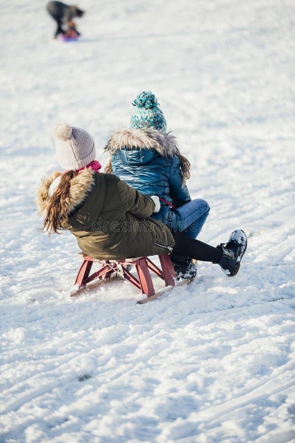 Δύο κορίτσια Sledding κάτω από το Hill στοκ εικόνα