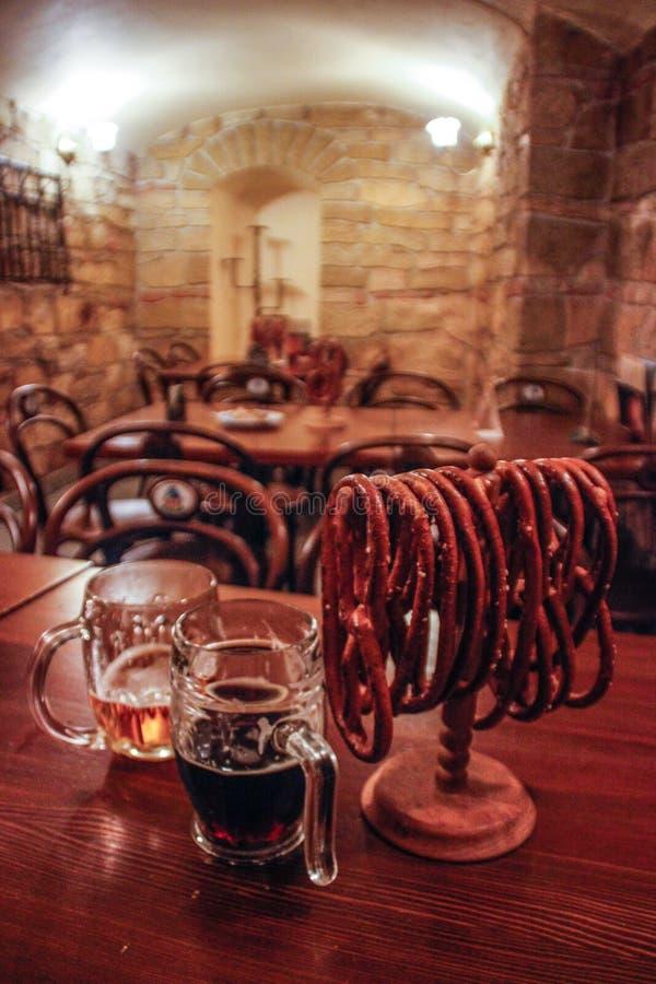 Δύο κούπες μπύρας και αλατισμένα pretzels στο υπόβαθρο του φραγμού στοκ εικόνες