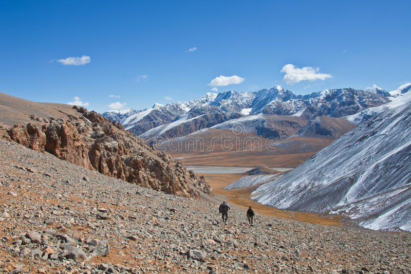 Δύο κυνηγοί μπαίνουν κάτω από το βουνό μέσα την κοιλάδα στοκ φωτογραφία με δικαίωμα ελεύθερης χρήσης