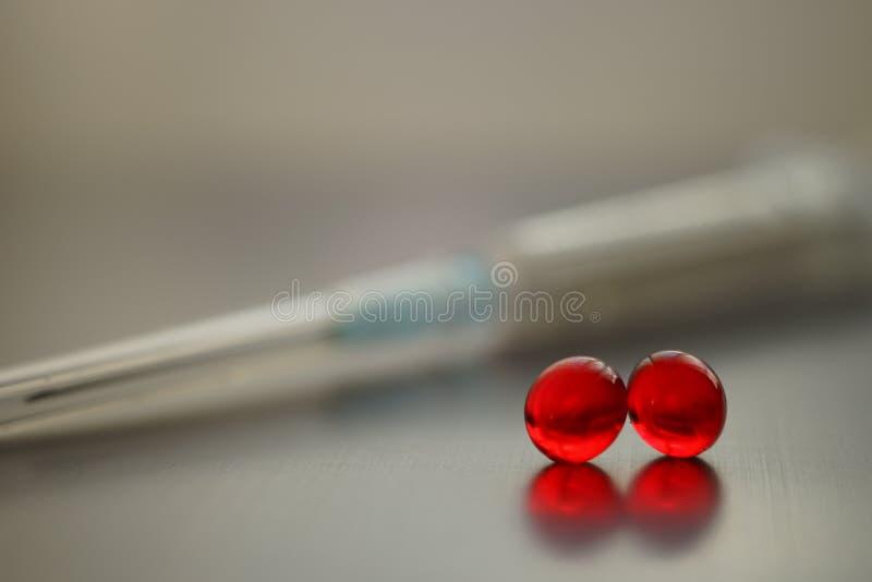 Δύο κόκκινες βιταμίνες και μία σύριγγα σε ένα τραπέζι από χρώμιο κλείνουν στοκ φωτογραφίες