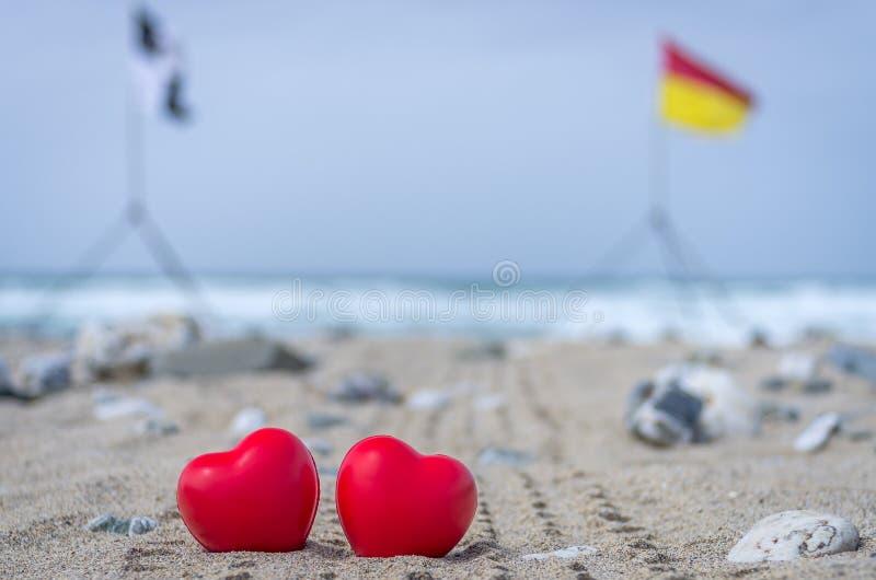 Δύο κόκκινες καρδιές στην παραλία με τις σημαίες κυματωγών στο υπόβαθρο στοκ φωτογραφίες με δικαίωμα ελεύθερης χρήσης