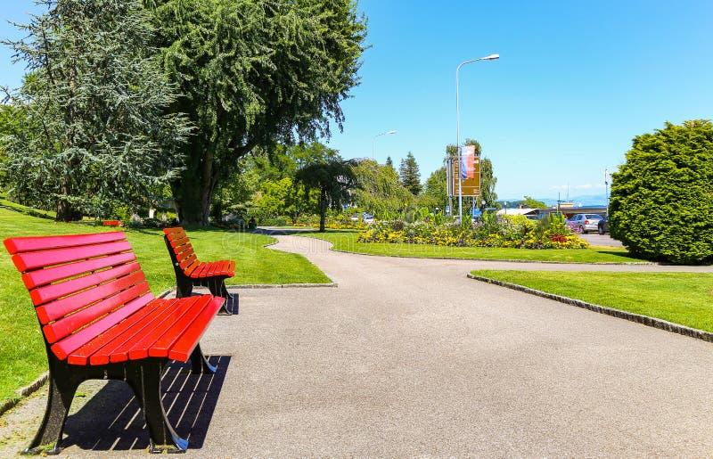 Δύο κόκκινοι πάγκοι στο όμορφο πάρκο στοκ εικόνα με δικαίωμα ελεύθερης χρήσης