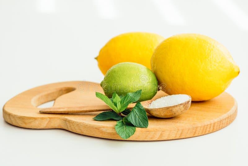 Δύο λεμόνια, ασβέστης, μέντα και ένα ξύλινο κουτάλι με το άλας στοκ φωτογραφία