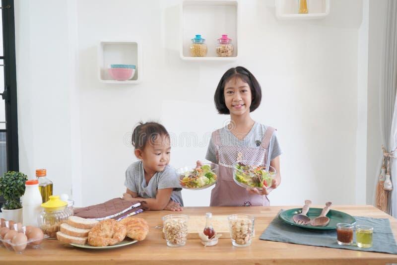 Δύο μάγειρες μικρών κοριτσιών στην κουζίνα στο σπίτι στοκ φωτογραφίες με δικαίωμα ελεύθερης χρήσης