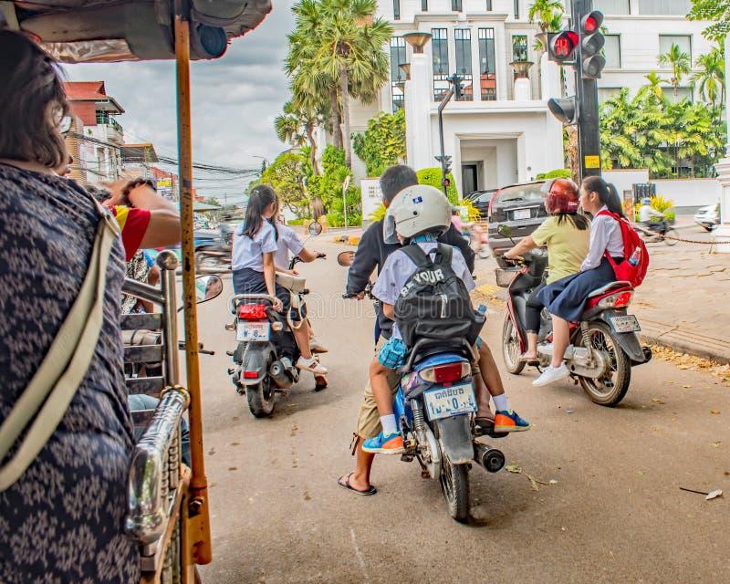 Δύο μαθήτριες που οδηγούν sidesaddle στο μηχανικό δίκυκλο γονέων τους στο σπίτι τρόπων από το σχολείο, ραφή συγκεντρώνουν την Καμ στοκ φωτογραφίες
