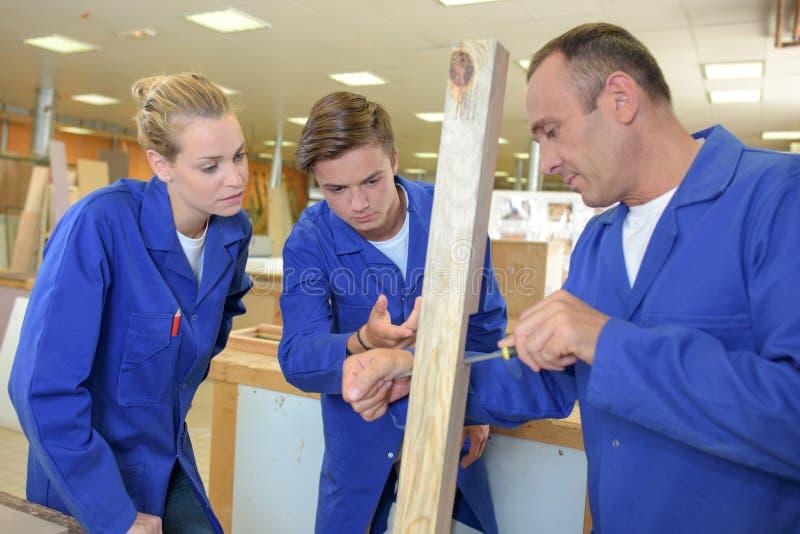 Δύο μαθητευόμενοι που προσέχουν τον ξυλουργό στην εργασία στοκ εικόνες