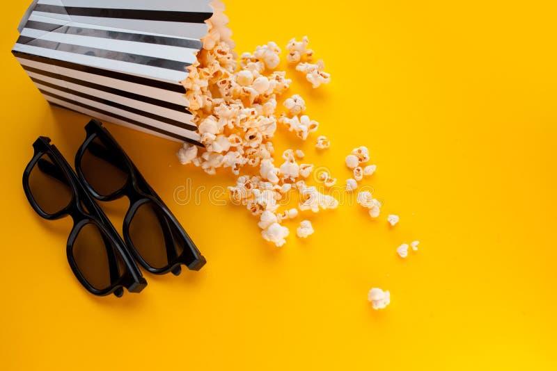 Δύο μαύρα τρισδιάστατα γυαλιά βρίσκονται δίπλα σε ένα γραπτό ριγωτό κιβώτιο papper popcorn, που διασκορπίζεται σε ένα κίτρινο υπό στοκ φωτογραφίες