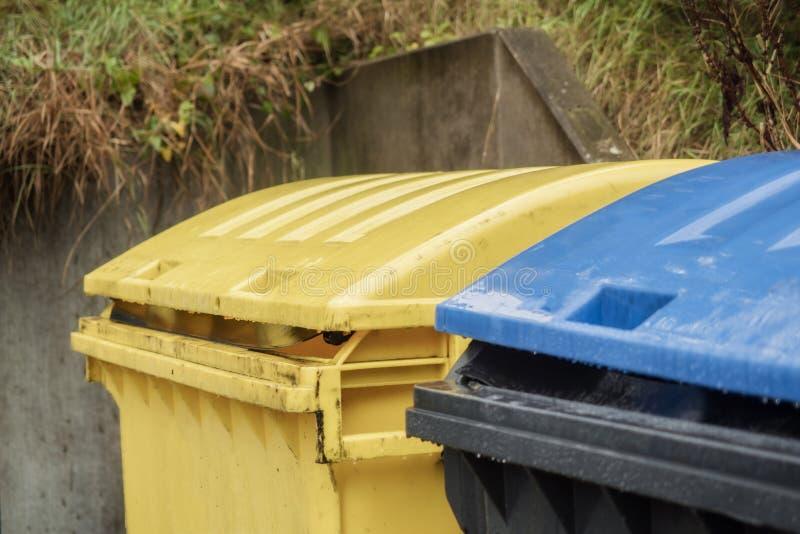 Δύο μεγάλα δοχεία απορριμάτων κίτρινος και μπλε-μαύρος στοκ εικόνα με δικαίωμα ελεύθερης χρήσης