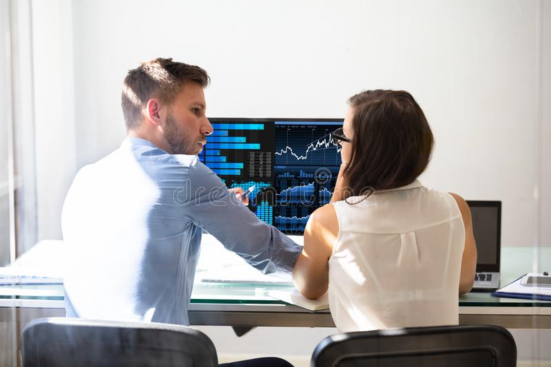 Δύο μεσίτες χρηματιστηρίου που συζητούν τις γραφικές παραστάσεις στον υπολογιστή στοκ φωτογραφία με δικαίωμα ελεύθερης χρήσης
