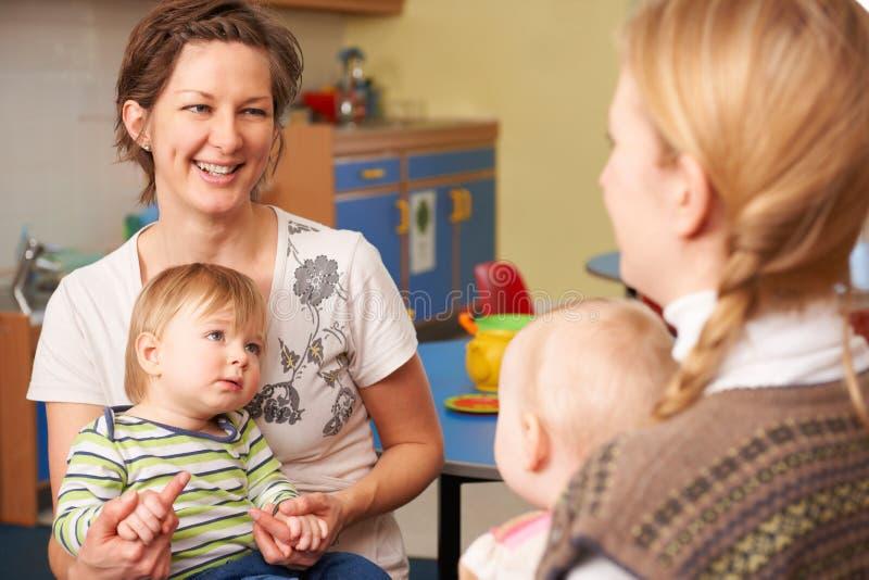 Δύο μητέρες με τα παιδιά που κουβεντιάζουν σε Playgroup στοκ εικόνα