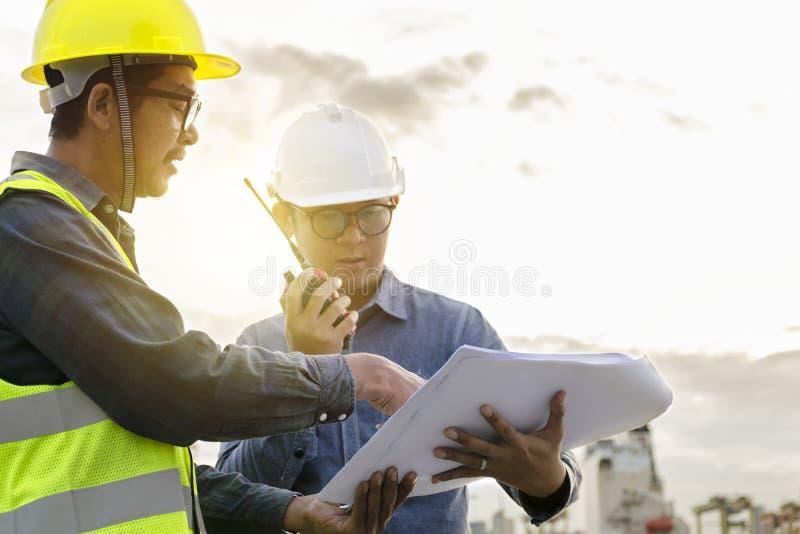 Δύο μηχανικοί είναι στον έλεγχο που χρησιμοποιεί τα εργαλεία ραδιοεπικοινωνίας και στοκ εικόνα