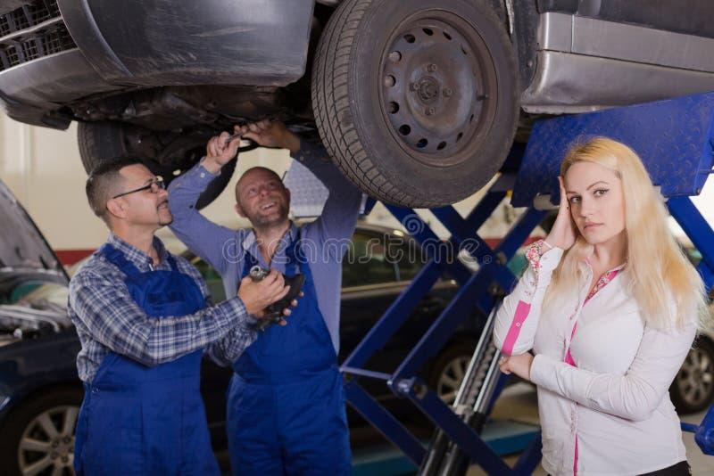 Δύο μηχανικοί που προσπαθούν να εξαπατήσει τον πελάτη στο εργαστήριο στοκ φωτογραφία