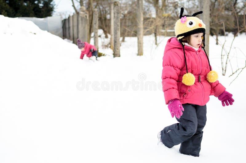 Δύο μικρά δίδυμα κορίτσια παίζουν στο χιόνι στοκ εικόνες με δικαίωμα ελεύθερης χρήσης