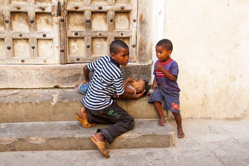 Δύο μικρά αφρικανικά αγόρια φροντίζουν το μικρότερο αδερφό τους στοκ εικόνα με δικαίωμα ελεύθερης χρήσης