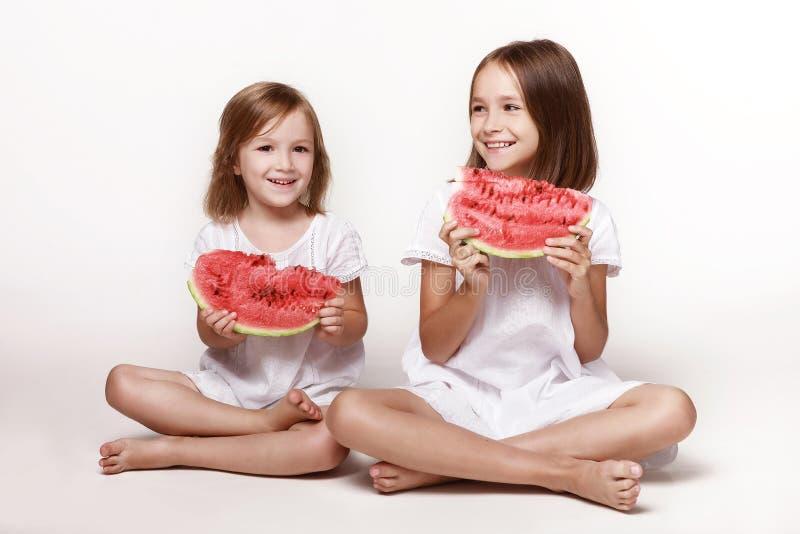 Δύο μικρά κορίτσια, αδερφές, κάθονται στο στούντιο σε λευκό φόντο με κομμάτια καρπούζι στοκ φωτογραφία