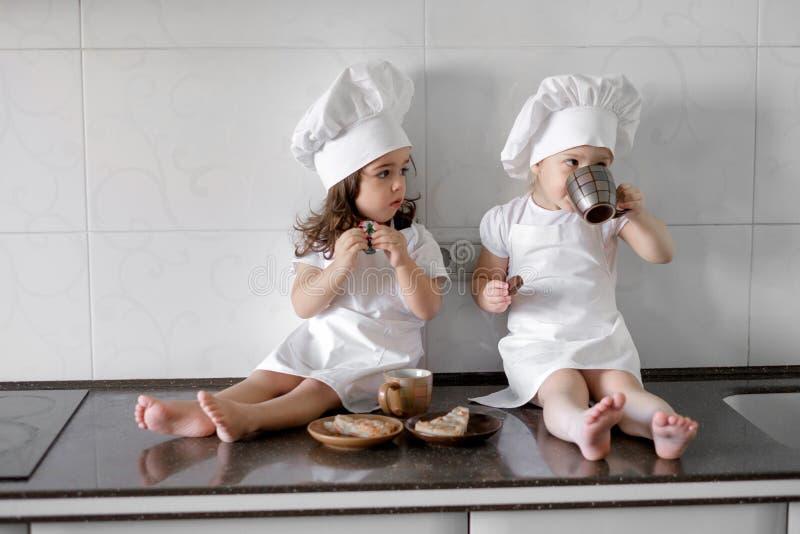 Δύο μικρά κορίτσια αρτοποιών πίνουν το τσάι με pabcakes στην κουζίνα στοκ φωτογραφία