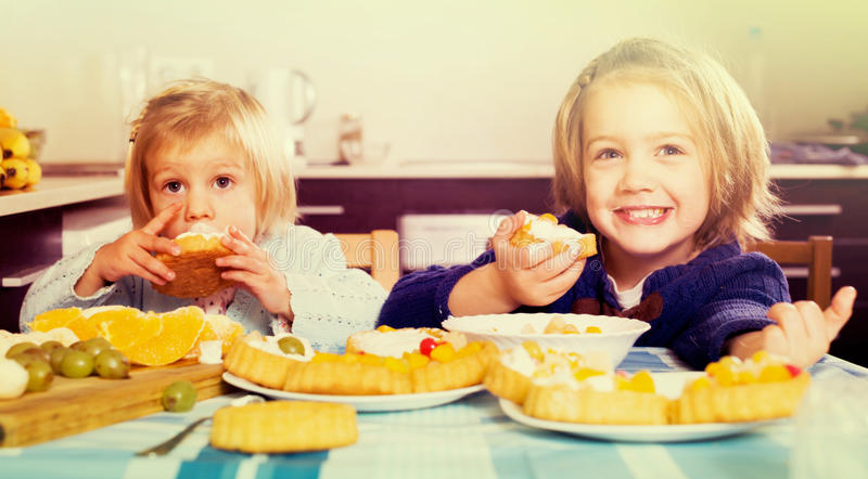 Δύο μικρά κορίτσια με τα επιδόρπια κρέμας στοκ εικόνες