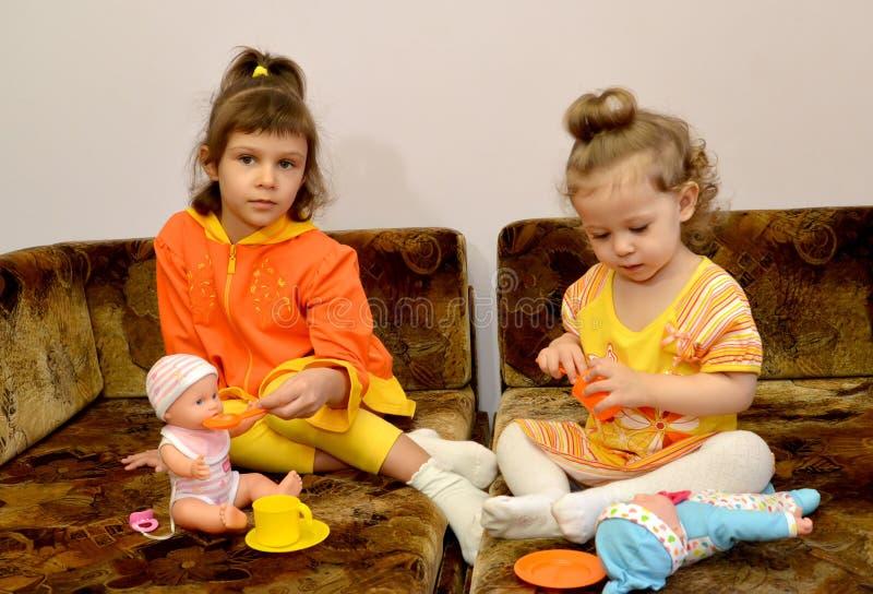 Δύο μικρά κορίτσια παίζουν με τις κούκλες σε έναν καναπέ στοκ εικόνες
