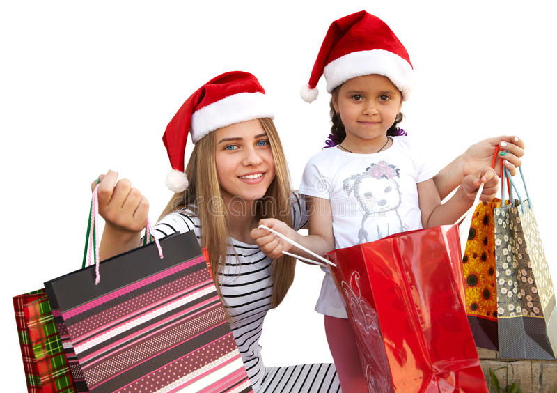 Δύο μικρά κορίτσια στην γούνα-ΚΑΠ με τις τσάντες αγορών Χριστούγεννα στοκ εικόνες