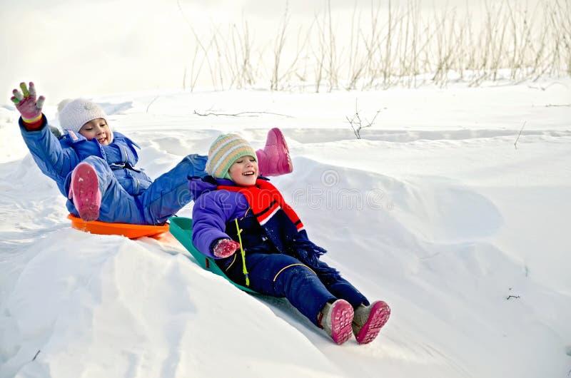 Δύο μικρά κορίτσια στο έλκηθρο μέσω του χιονιού για να γλιστρήσει στοκ εικόνες