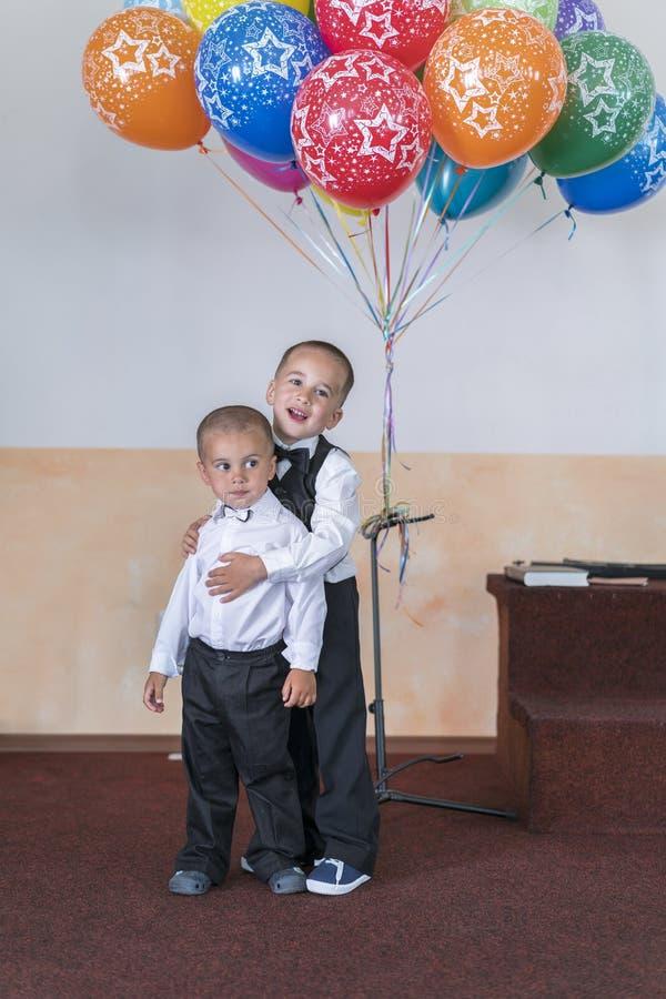 Δύο μικρά παιδιά και μπαλόνια Δύο αδελφοί στη σκηνή στα ακριβή κοστούμια στοκ εικόνες