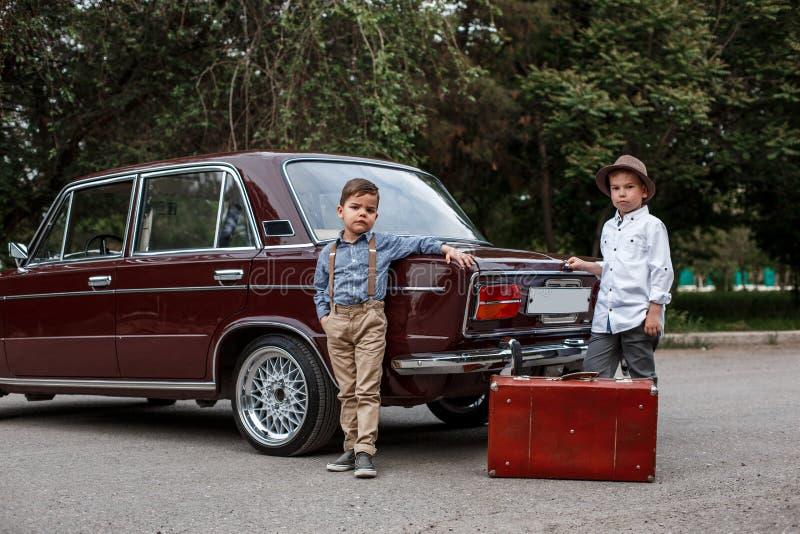 Δύο μικρά παιδιά στα εκλεκτής ποιότητας ενδύματα υπερασπίζονται το αναδρομικό αυτοκίνητο στοκ εικόνες