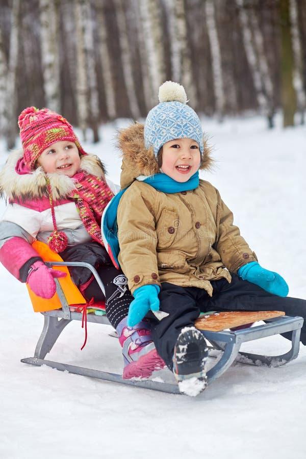 Δύο μικρά παιδιά κάθονται στο έλκηθρο στοκ φωτογραφία