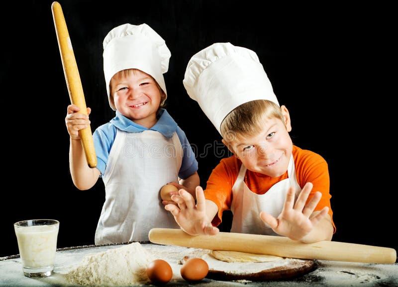 Δύο μικρά παιδιά που κατασκευάζουν τη ζύμη πιτσών ή ζυμαρικών στοκ εικόνες