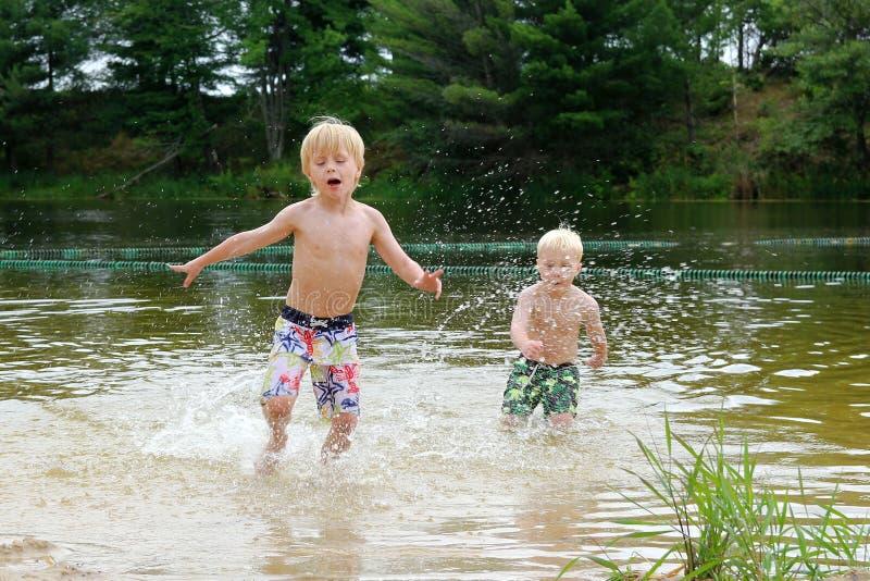 Δύο μικρά παιδιά που κολυμπούν και που παίζουν στη λίμνη στοκ εικόνες με δικαίωμα ελεύθερης χρήσης