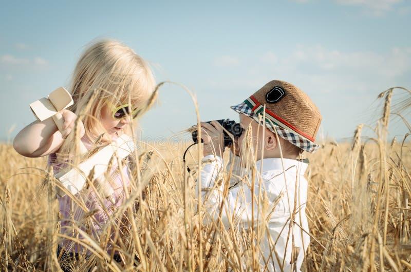 Δύο μικρά παιδιά που παίζουν σε έναν τομέα σίτου στοκ εικόνες