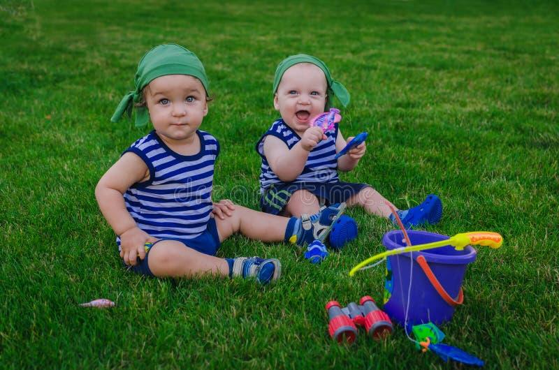 Δύο μικρά παιδιά που παίζουν στους ψαράδες μικρών παιδιών που κάθονται στο fre στοκ φωτογραφίες