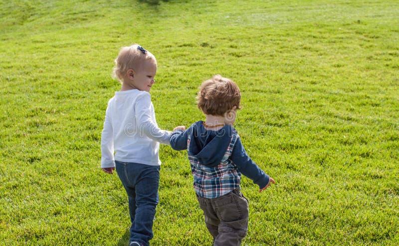 Δύο μικρά παιδιά, που περπατούν χέρι-χέρι στη χλόη στοκ φωτογραφία