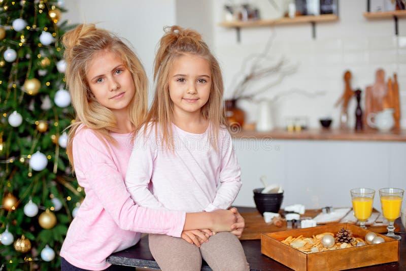 Δύο μικρές αδελφές κάθονται στην κουζίνα στα πλαίσια του χριστουγεννιάτικου δέντρου Πρωί της ημέρας των Χριστουγέννων στοκ εικόνες