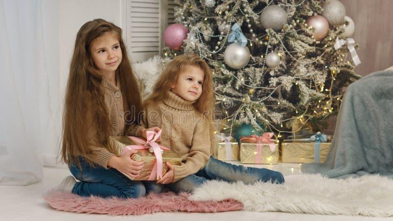 Δύο μικρές αδελφές στο χριστουγεννιάτικο δέντρο στοκ φωτογραφίες