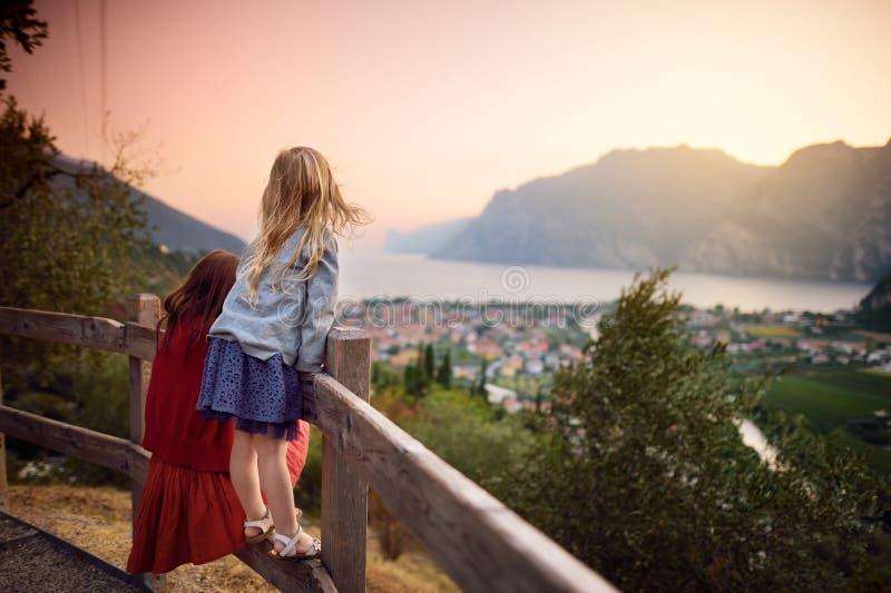 Δύο μικρές αδελφές που απολαμβάνουν τη φυσική εναέρια θέα Riva del Garda της πόλης, που βρίσκεται σε μια ακτή της λίμνης Garda στοκ εικόνες