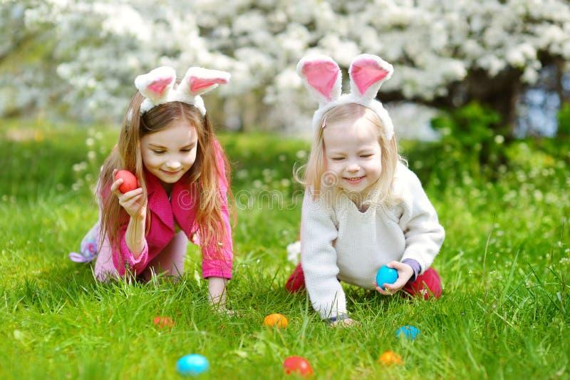 Δύο μικρές αδελφές που κυνηγούν για το αυγό Πάσχας την ημέρα Πάσχας στοκ φωτογραφίες