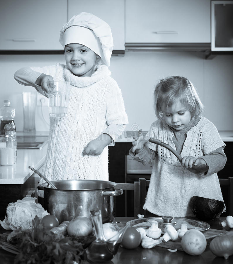 Δύο μικρές αδελφές που μαθαίνουν πώς να μαγειρεψει στοκ φωτογραφία