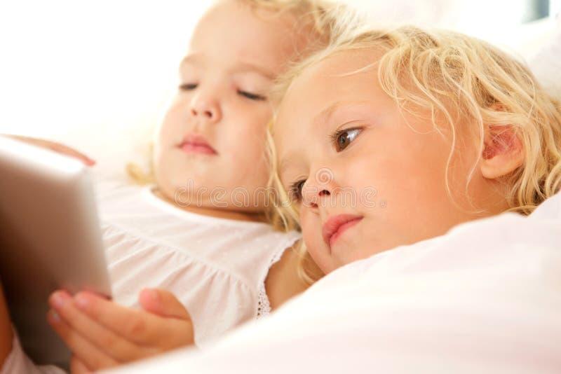 Δύο μικρές αδελφές που χρησιμοποιούν την ψηφιακή ταμπλέτα στοκ φωτογραφία με δικαίωμα ελεύθερης χρήσης