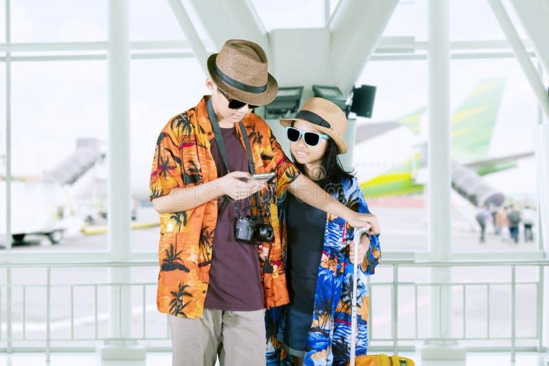 Δύο μικροί τουρίστες που χρησιμοποιούν ένα τηλέφωνο στον αερολιμένα στοκ φωτογραφία