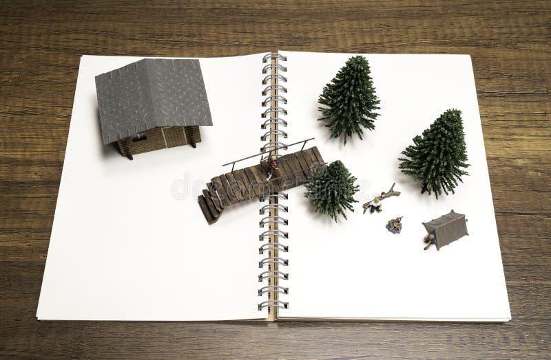 Δύο μικρογραφίες που στρατοπεδεύουν με το δέντρο, τη γέφυρα και το σπίτι πεύκων στο άσπρο κενό σημειωματάριο στοκ φωτογραφίες
