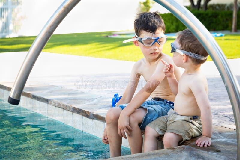 Δύο μικτά σημεία μωρών αγώνων κινεζικά καυκάσια στον αδελφό που φορά τα κολυμπώντας προστατευτικά δίοπτρα στοκ εικόνες με δικαίωμα ελεύθερης χρήσης