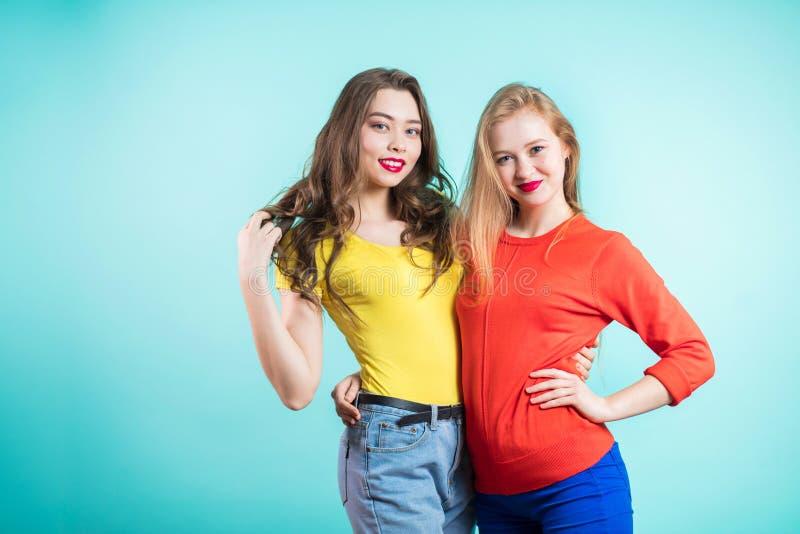Δύο μοντέρνες γυναίκες στα φωτεινά ενδύματα στο μπλε υπόβαθρο στοκ φωτογραφία με δικαίωμα ελεύθερης χρήσης