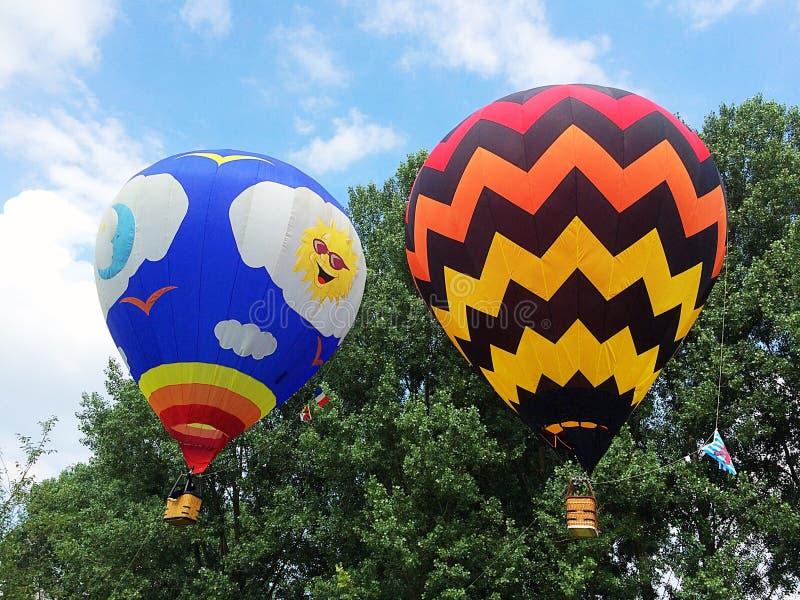 Δύο μπαλόνια ζεστού αέρα μπροστά από τα δέντρα στο φως ημέρας στοκ εικόνες