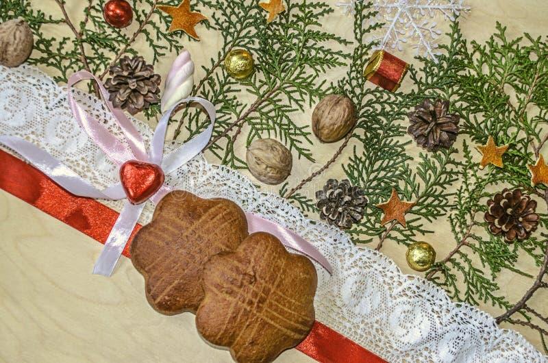 Δύο μπισκότα με την κόκκινες κορδέλλα και τη δαντέλλα τακτοποιούν, καρδιά σοκολάτας στα τόξα και τους κλαδίσκους του thuja στοκ εικόνα με δικαίωμα ελεύθερης χρήσης