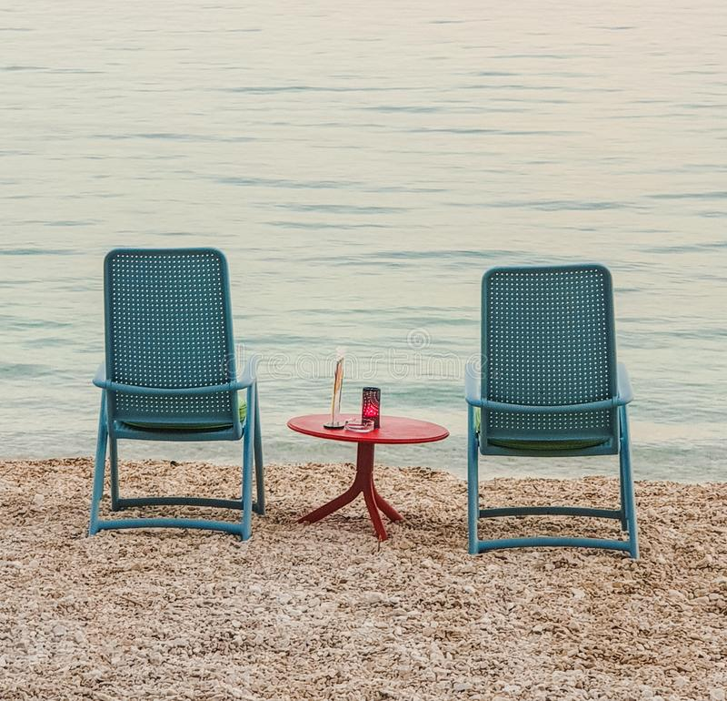 Δύο μπλε καρέκλες με έναν κόκκινο πίνακα στη μέση που στέκεται στην παραλία χαλικιών της αδριατικής θάλασσας το καλοκαίρι σε ένα  στοκ εικόνα με δικαίωμα ελεύθερης χρήσης