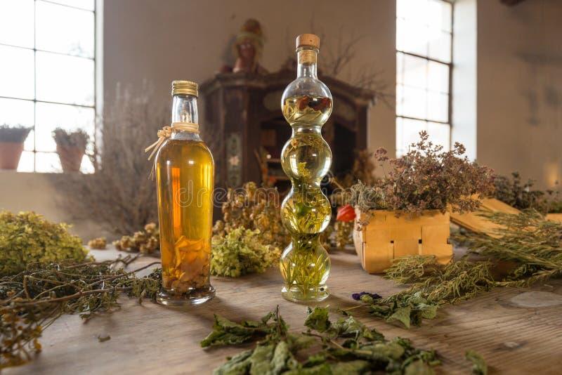 Δύο μπουκάλια με το πετρέλαιο σε έναν πίνακα με τα ξηρά χορτάρια και τα λουλούδια στοκ εικόνες με δικαίωμα ελεύθερης χρήσης